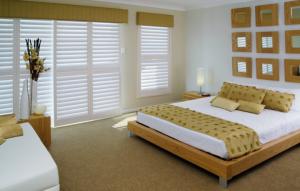 Sliding-White-Timber-Shutters-in-Bedroom-e1428747544184