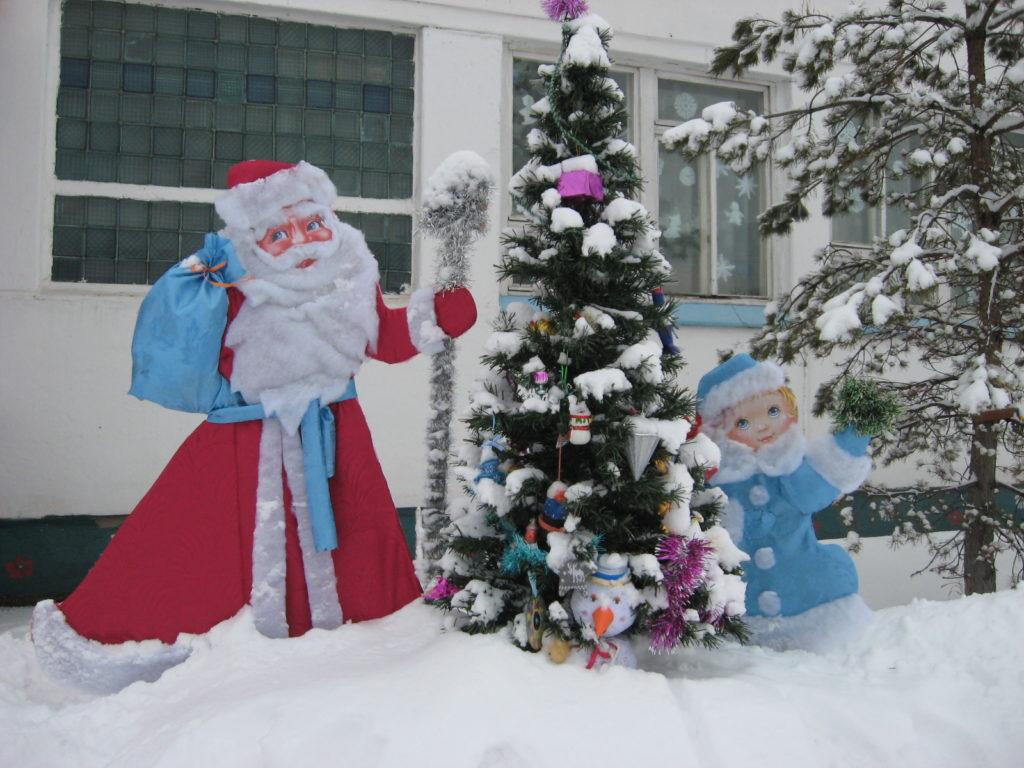 Фигуры Деда Мороза и снегурочки рядом с Елочкой